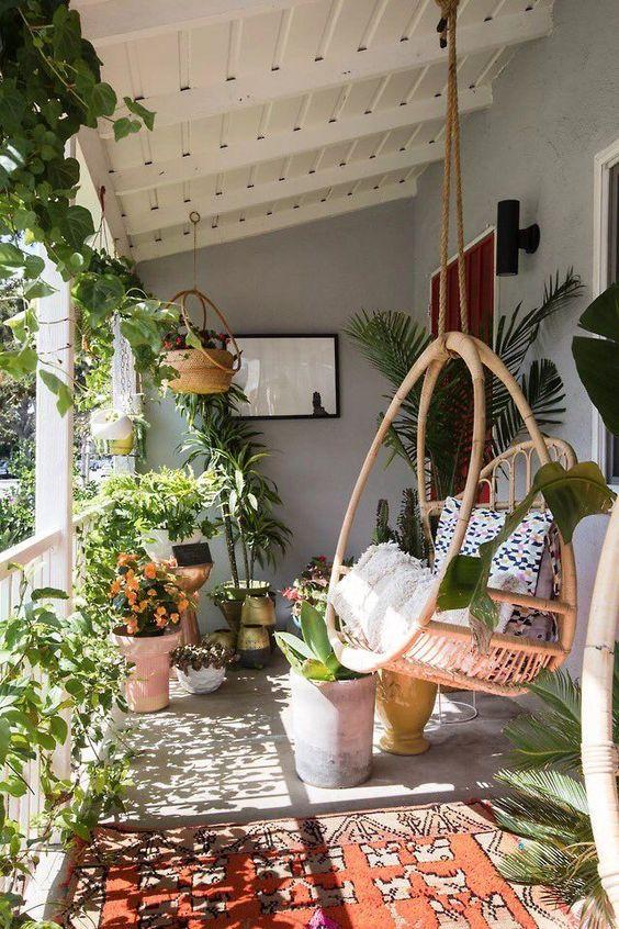 Balcon avec fauteuil suspendu style bohème et des plantes
